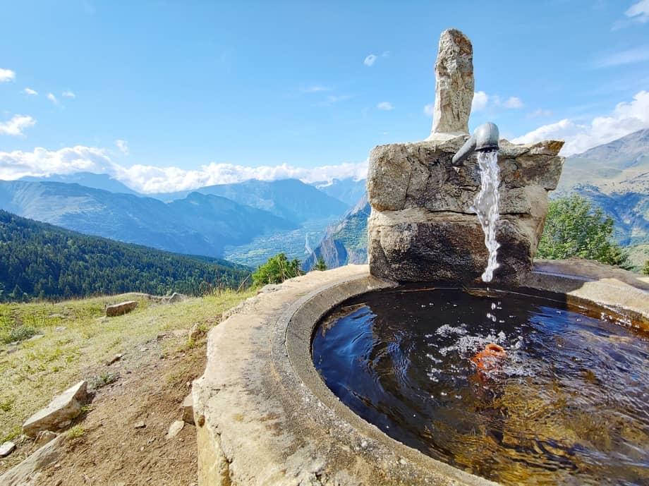 Fontaine et vue sur Bourg d'Oisans, montagne